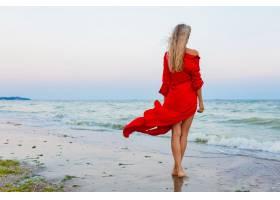 紅色禮服的美麗的自由婦女在風的風在海灘走_13977783