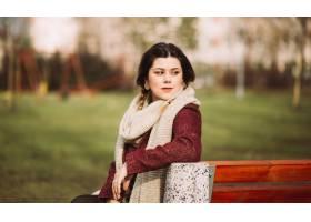 美丽的俏丽的深色的女孩微笑的画象坐长凳_15915150