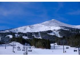 在雪盖的小山和森林围拢的索道风景在蓝天下_15914750