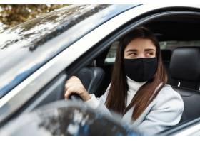 坐在汽车的少妇司机驾驶在面罩上工作_13869212