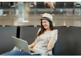 坐在膝上型计算机的年轻快乐的旅客旅游妇女_15792456