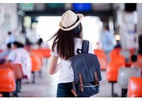 微笑与地图和袋子的美丽的亚裔妇女在公共汽_5017107