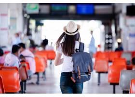 微笑与地图和袋子的美丽的亚裔妇女在公共汽_5017108