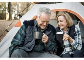 愉快的年长夫妇夫妇咖啡由帐篷在森林里_13307639