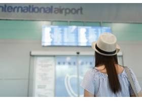 戴帽子的年轻旅客旅游妇女后面图看在日程表_15792268