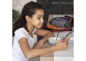 检查她的电话的女孩当吃早餐_14277319