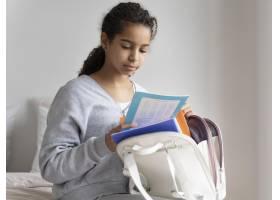 检查她的笔记的女孩在学校_14277348