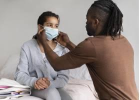 父亲帮助他的女儿放她的医疗面具_14277359