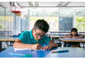 玻璃的被聚焦的年轻男孩坐在书桌上和在类的_13996164