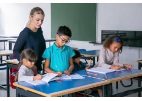 看孩子的正面女性学校老师在类的课上做他们_13996263