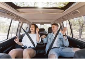 中等射击愉快的夫妇跳舞在汽车里面_9685823