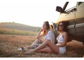 坐在汽车旁边的金发和卷发的微笑的女士_13291275