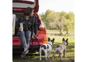 坐在汽车的逗人喜爱的小狗和妇女_10825557