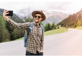 棕色帽子的微笑的人站立用在口袋的手和做se_10561752
