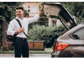 站立乘汽车的年轻英俊的商人与旅行袋子_9320356