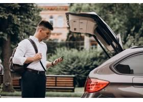 站立乘汽车的年轻英俊的商人与旅行袋子_9320359