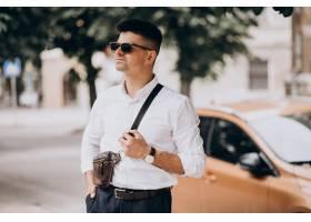 站立他的汽车的英俊的商人在商务旅行_9320334