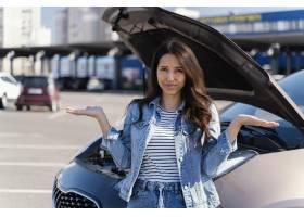 站立在她的残破的汽车旁边的妇女_13919516
