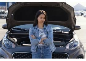 站立在她的残破的汽车旁边的妇女_13919525