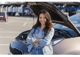 站立在她的残破的汽车旁边的妇女_13919526