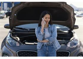 站立在她的残破的汽车旁边的妇女_13919543