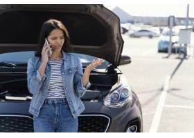 站立在她想到众多的残破的汽车旁边的妇女_13919548