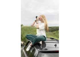 站立在汽车和采取�自然图片的妇女侧视图_8924136