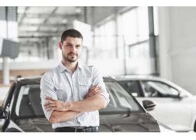 站立在汽车的汽车沙龙的英俊的☆年轻人顾问_10514658