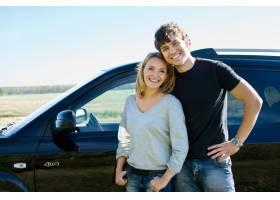 站立在汽车附近的愉快的美好的年轻夫妇_10880327