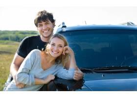 站立在汽车附近的愉快的美好的年轻夫妇_11182036