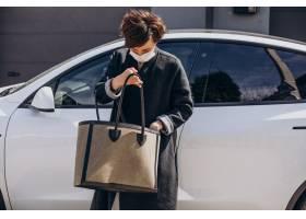 站立由她的汽车的妇女佩带的面罩那人脑袋震荡了下_15037963