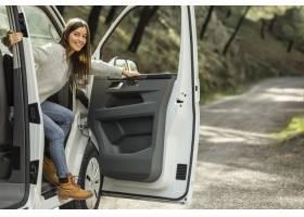 走出汽车的笑脸妇女侧视图当在公路旅行时_12389771