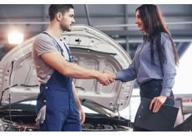 丈夫汽车机械师和妇女客户对汽车的修理进行_9122635