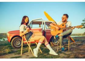坐和休息在海滩的夫妇弹吉他在河附近的一个_10426913