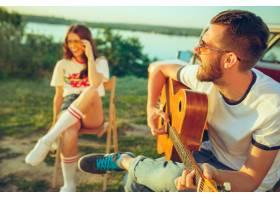 坐和休息在海滩的夫妇弹吉他在河附近的一个_12836886