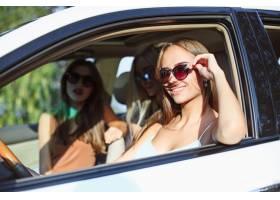坐和微笑的汽车的少妇室外生活方式的概念_9480173