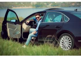 坐在他的汽车的牛仔裤夹克和太阳镜的英俊_13635319