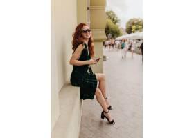 坐在外面和微笑的绿色礼服和太阳镜的夫人_12728311