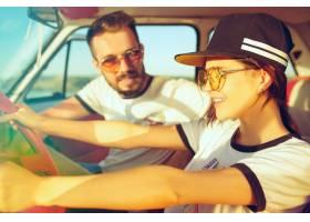 坐在汽车的笑浪漫夫妇当在公路旅行时_13055409