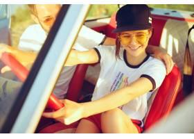 坐在汽车的笑的浪漫夫妇当在公路旅行时_10426901