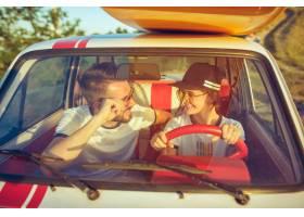 坐在汽车的笑的浪漫夫妇当在公路旅行时_10426902