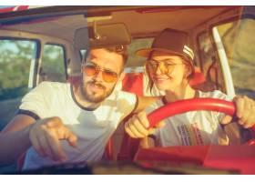 坐在汽车的笑的浪漫夫妇当在公路旅行时_12046029