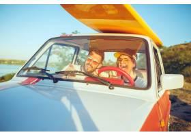 坐在汽车的笑的浪漫夫妇当在公路旅行时_12046030