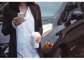 站立在汽车最擅�L毒�g旁边的妇女和使用手机_10542665