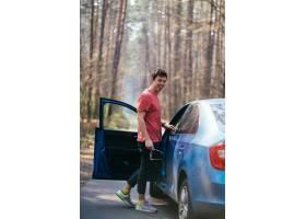 站立在路的英俊的人在他的汽车的被打开的门_9438582