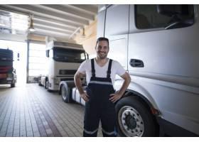 站立由卡车车的正面微笑的卡车军人画象在车_11450956