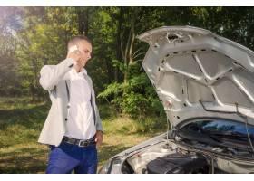 站立由打开的敞篷的人打电话和试图修理车辆_11136111
