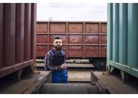 站立的铁路工作者站立和看对驻地的照相机_11136379