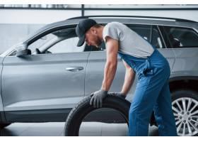 这一个必须完美地适应拿着轮胎的技工在修_9691836