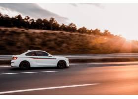 驾驶在�K路的白色小轿车轿车在日落_6143817